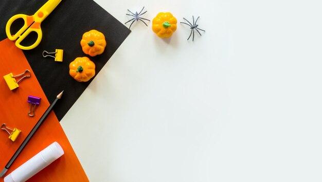 Stukjes papier voor halloween. handgesneden papier. pompoenen. schaar en lijm. op een lichte achtergrond. bovenaanzicht.
