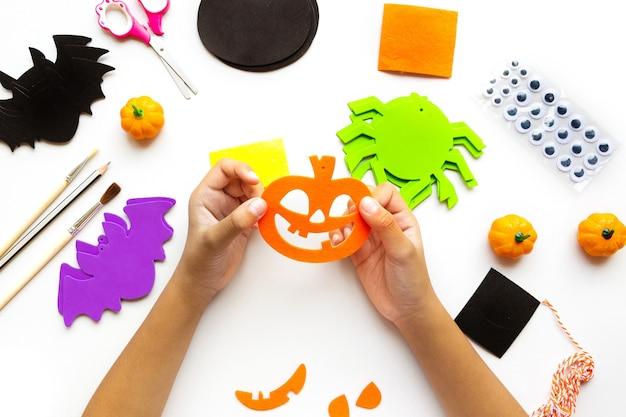 Stukjes papier voor halloween. handgesneden papier. pompoenen, vleermuizen en spinnen schaar en lijm. op een lichte achtergrond. bovenaanzicht. plat leggen. doe-het-zelf. stap voor stap