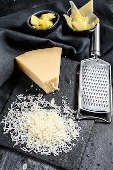 Stukjes parmigiano reggiano harde kaas. in plakjes gesneden, gesneden, geraspt. zwarte achtergrond. bovenaanzicht.