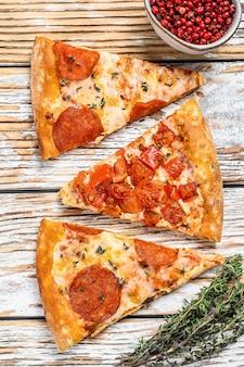 Stukjes pepperoni en tomatenpizza. witte houten achtergrond. bovenaanzicht.