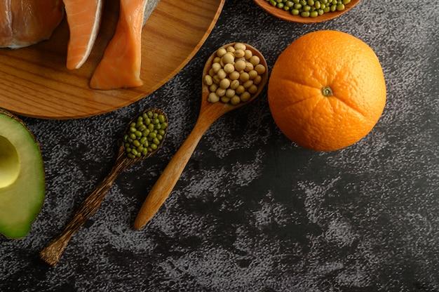 Stukjes peulvruchten, fruit en zalm op een houten bord.