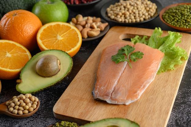 Stukjes peulvruchten, fruit en zalmvissen op een houten snijplank.