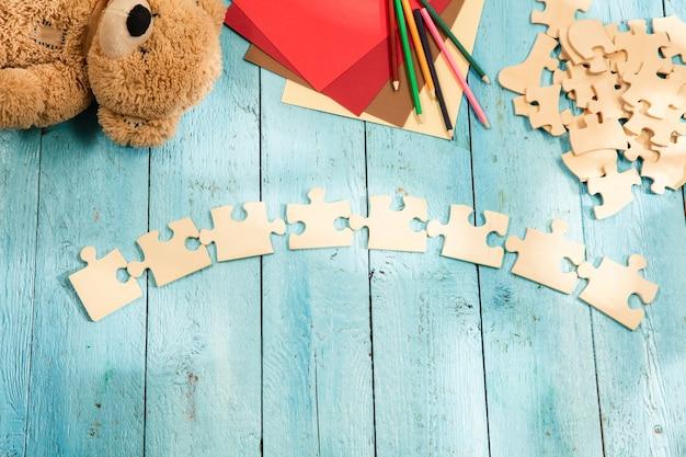 Stukjes puzzels op het oppervlak van een houten tafel met speelgoed en kleuren