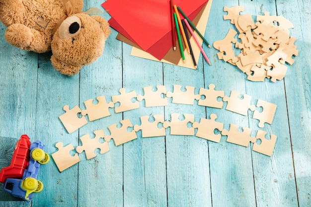 Stukjes puzzels op het oppervlak van een houten tafel met speelgoed en kleuren Gratis Foto