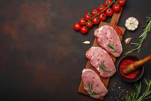 Stukjes rauw varkensvlees steak met basilicum, cherrytomaatjes, rozemarijn, knoflook, peper, zout en specerijen mortel op snijplank en roestige bruine achtergrond met ruimte voor uw tekst