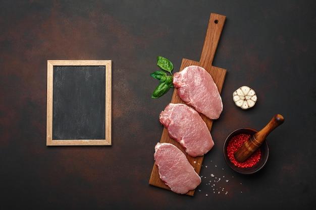 Stukjes rauw varkensvlees steak met basilicum, knoflook, peper, zout en kruidenmortier en krijtbord op snijplank en roestige bruine achtergrond met ruimte voor uw tekst