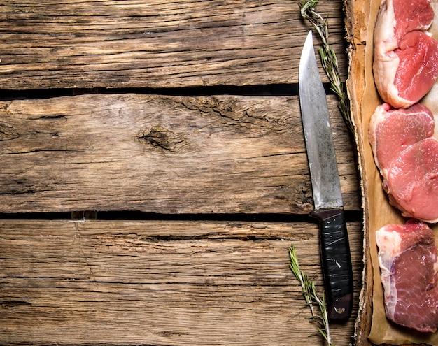Stukjes rauw vlees met een slagersmes. op houten achtergrond. vrije ruimte voor tekst. bovenaanzicht