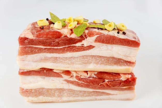 Stukjes rauwe varkensbuik met knoflook geïsoleerd op een witte achtergrond.