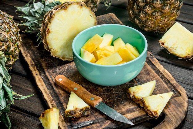 Stukjes rijpe ananas in een kom op een snijplank met een mes. op houten