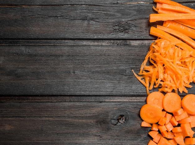 Stukjes rijpe wortelen. op zwarte houten achtergrond