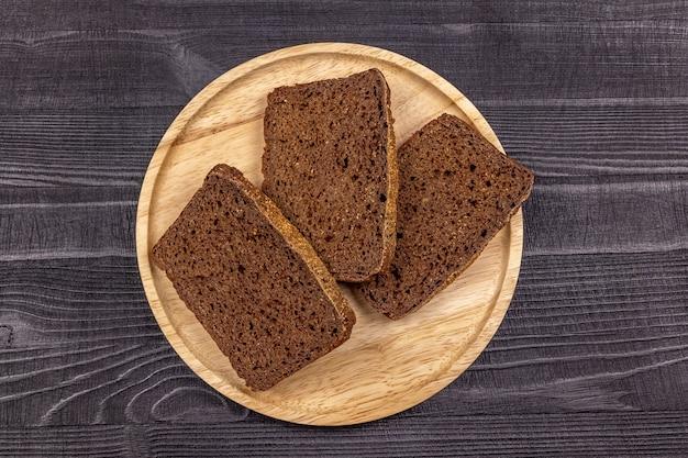 Stukjes roggemeel zwart brood op een houten serveerschaal en zwarte rustieke achtergrond. bovenaanzicht.