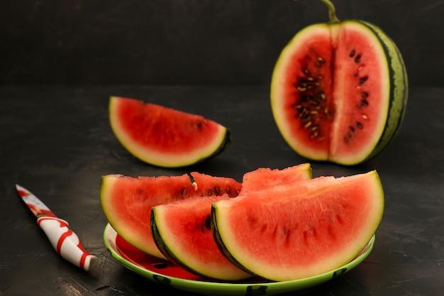 Stukjes sappige watermeloen bevinden zich op een bord op een donkere achtergrond. er ligt ook een mes op tafel. horizontale foto.