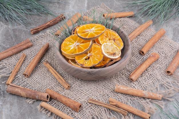 Stukjes sinaasappel in een houten kop met rond pijpjes kaneel