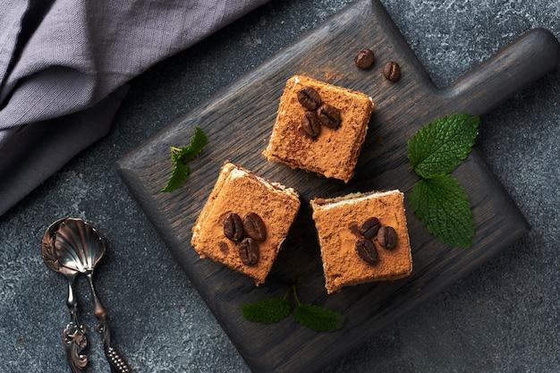 Stukjes tiramisu-cake met delicate room, koffiebonen en muntblaadjes. bovenaanzicht