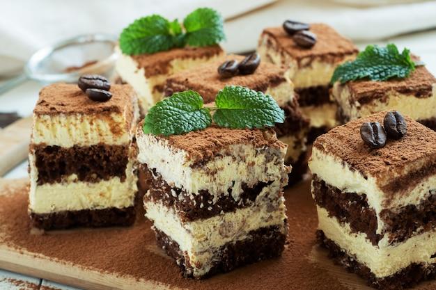 Stukjes tiramisu-cake met delicate room, koffiebonen en muntblaadjes.