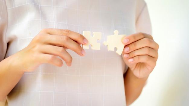 Stukjes van de puzzel in de handen van de vrouw
