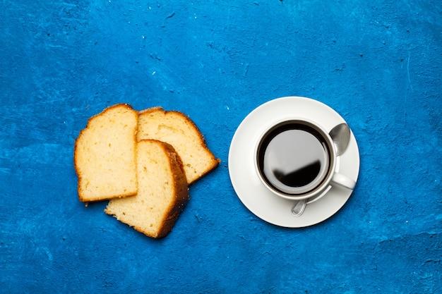 Stukjes vanillecake en een kopje koffie op een klassieke blauwe achtergrond in een bovenaanzicht