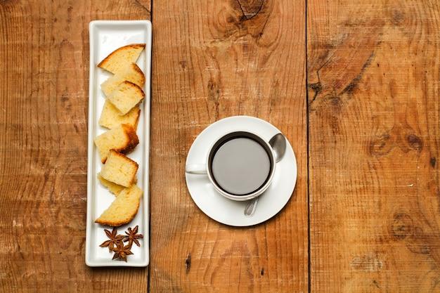 Stukjes vanillecake en een kopje koffie op een rustieke houten tafel