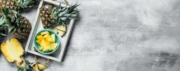 Stukjes verse ananas in een kom op dienblad. op rustieke ondergrond