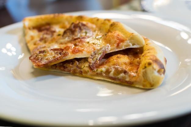 Stukjes verse hete pizza met pepperonisworst en mozzarellakaas bestrooid met kruiden. selectieve aandacht