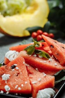 Stukjes verse rode watermeloen op een zwarte plaat