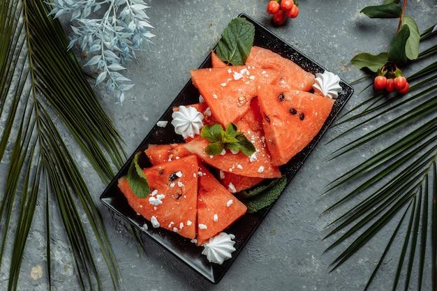 Stukjes verse rode watermeloen op een zwarte plaat Premium Foto