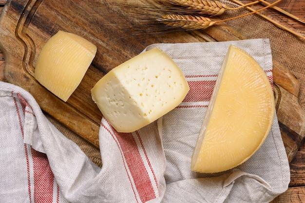 Stukjes verse zelfgemaakte italiaanse kaas op een houten tafelblad bekijken