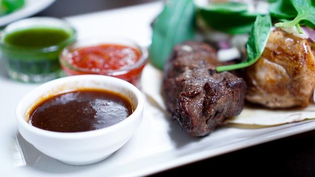 Stukjes vlees met uien op spiesjes kebab. serveer met saus op een wit bord.