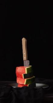 Stukjes watermeloen op een zwarte achtergrond en een mes. rustieke stijl.
