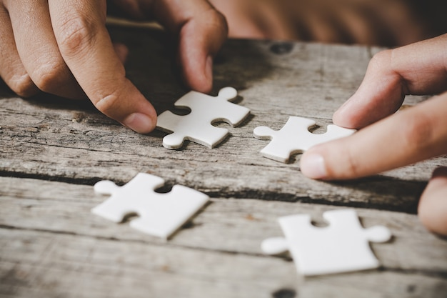 Stukjes witte puzzel op hout