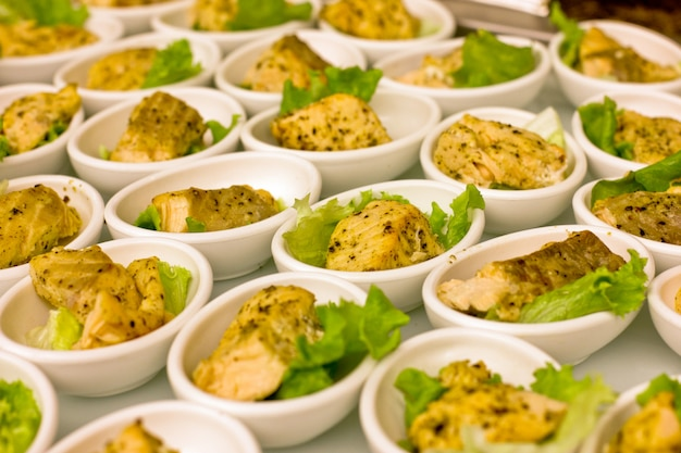 Stukjes witvis gegrild, geserveerd in witte kommen, versierd met slablaadjes