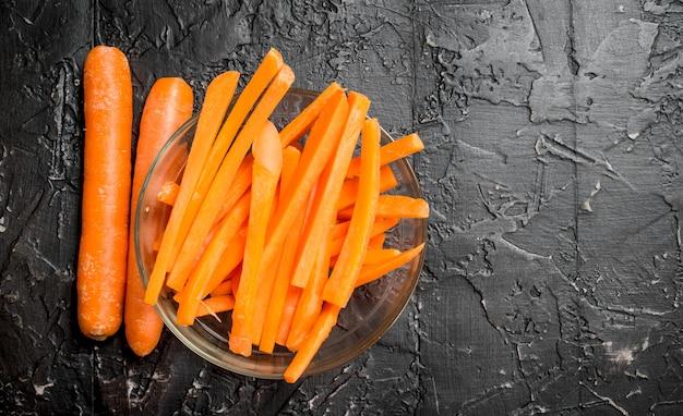 Stukjes wortelen op een kom. op zwarte rustiek