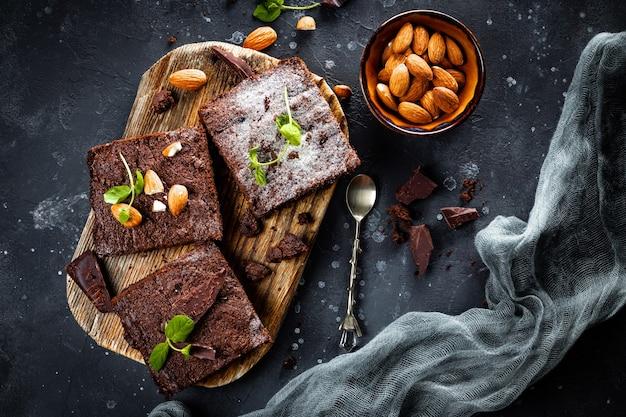Stukjes zelfgemaakte chocolade brownie met muntblaadjes en noten op de grijze achtergrond, bovenaanzicht