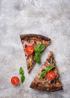 Stukjes zwarte pizza met tomaten en basilicum