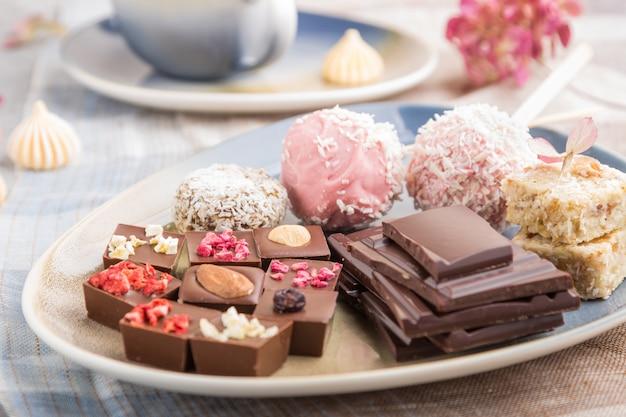 Stukken eigengemaakte chocolade met kokosnotensuikergoed op een blauw en bruin textiel. zijaanzicht
