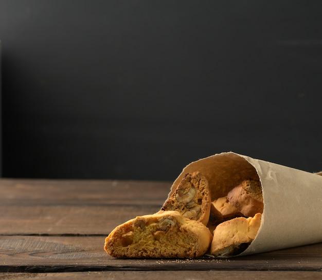 Stukken gebakken italiaanse biscottikoekjes, houten tafel, exemplaarruimte