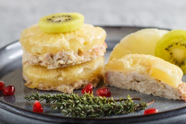 Stukken gebakken varkensvlees met ananas, kaas en kiwi op grijze plaat.