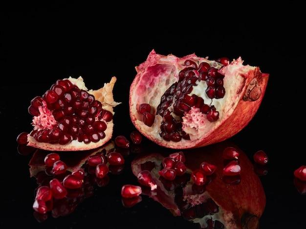 Stukken gebroken granaatappel fruit op een zwarte glanzende achtergrond