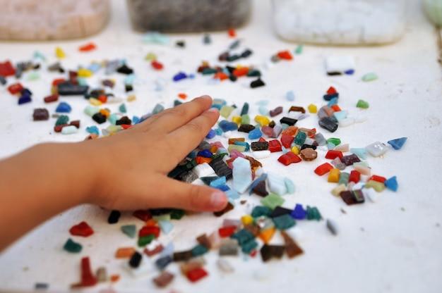 Stukken gekleurd glasmozaïek in de hand van het kind op de tafel