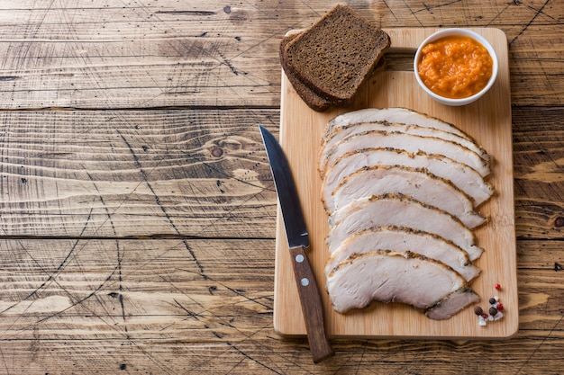 Stukken gerookt gekookt varkensvlees op een houten rustieke raad