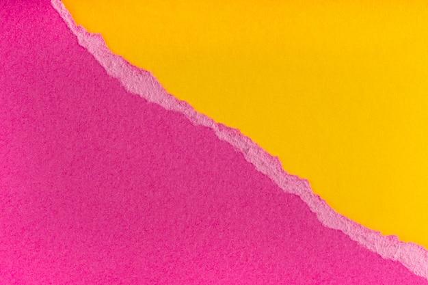 Stukken gescheurde haveloze paarse papieren randen op gele achtergrond.