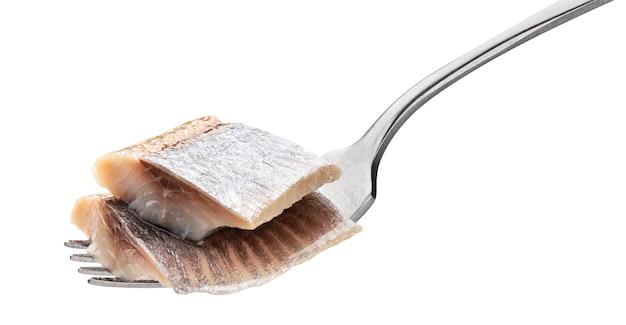 Stukken gezouten haring op vork die op wit met het knippen van weg, gemarineerd makreelvisfilet wordt geïsoleerd