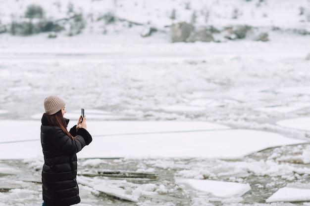 Stukken ijs op een bevroren rivier. meisje neemt de foto op smartphone bij verbazingwekkend landschap.