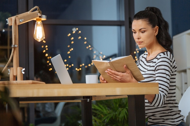 Stukken informatie. aantrekkelijke positieve jonge vrouw aan de tafel zitten en notities lezen terwijl ze op het werk