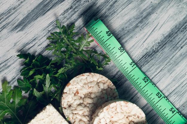 Stukken knäckebrood dichtbij meetlint en groene rucola op grijs.