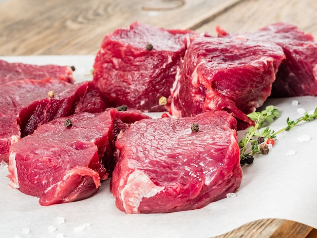 Stukken onbewerkte striploin. ruw rundvlees met kruiden op perkamentdocument op houten achtergrond