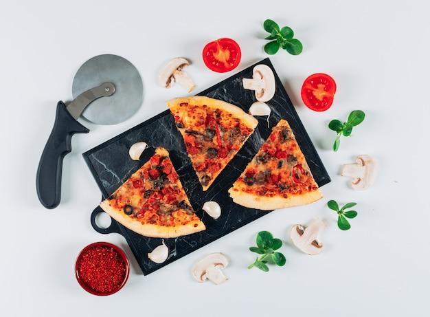 Stukken pizza met tomaat en knoflook, kruiden, champignons, muntblaadjes en een pizzasnijder in een snijplank op lichtblauwe achtergrond, plat.