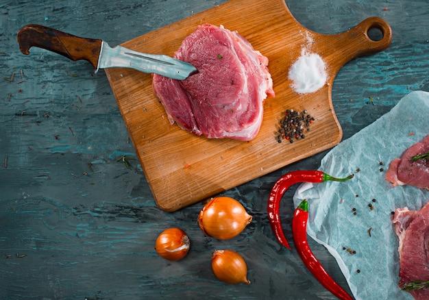 Stukken rauw varkensvlees steak met specerijen en kruiden rozemarijn