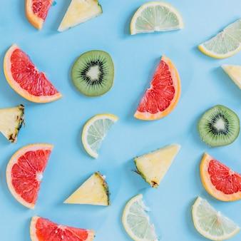 Stukken van ananassen en kiwi dichtbij citrusvruchten