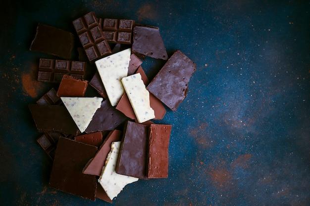Stukken van donkere, witte en melkchocolade. bovenaanzicht